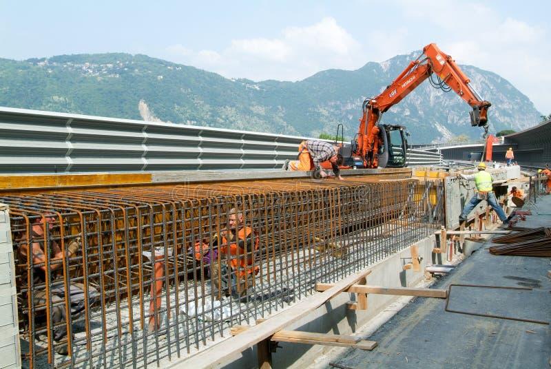 Lavoratore che lega tondo per cemento armato per costruzione di una strada principale fotografia stock