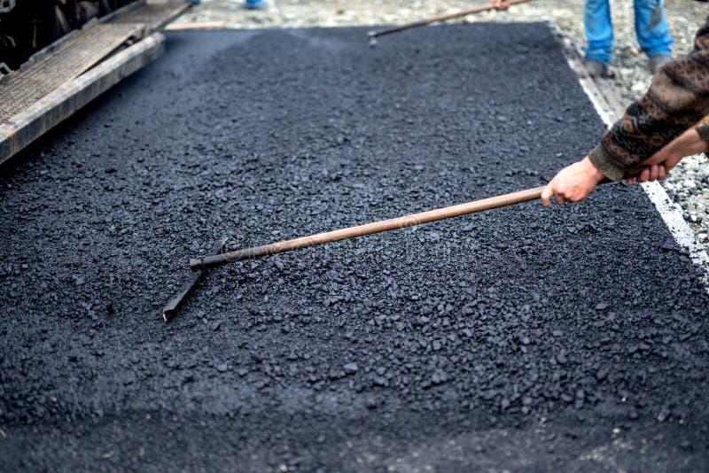 Lavoratore che livella asfalto fresco su un sito della for Costruzione di un pollaio su ruote