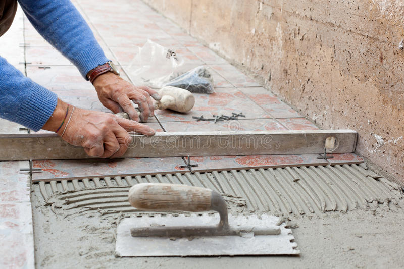 Lavoratore che livella nuova pavimentazione con uno strumento specifico fotografia stock libera da diritti