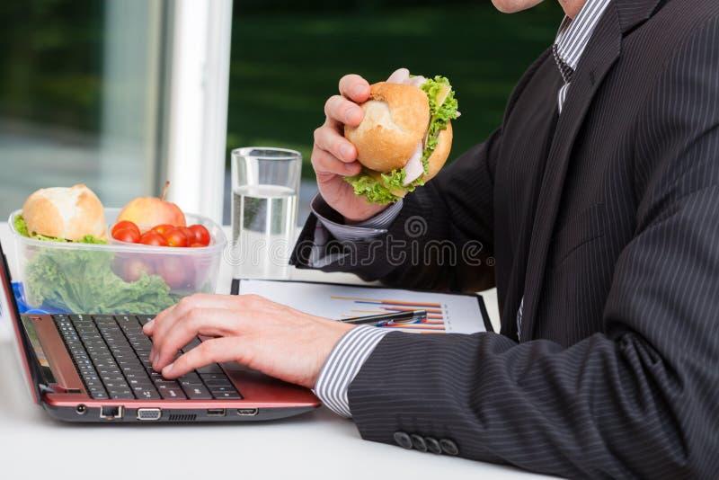 Lavoratore che mangia al suo scrittorio fotografie stock libere da diritti