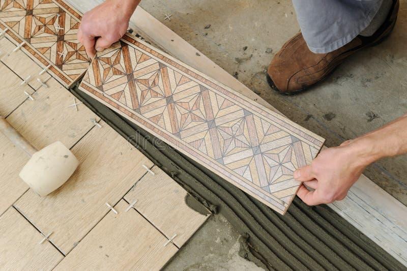 Lavoratore che mette le mattonelle sul pavimento immagini stock
