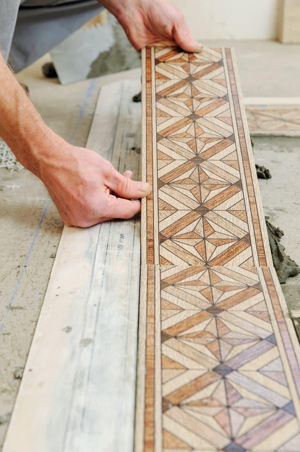 Lavoratore che mette le mattonelle sul pavimento immagine stock libera da diritti