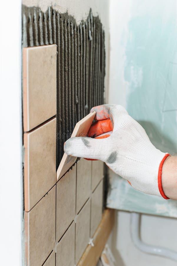 Lavoratore che mette le mattonelle sulla parete nella cucina immagini stock libere da diritti