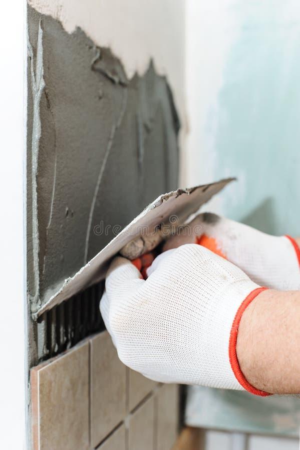 Lavoratore che mette le mattonelle sulla parete nella cucina fotografia stock libera da diritti