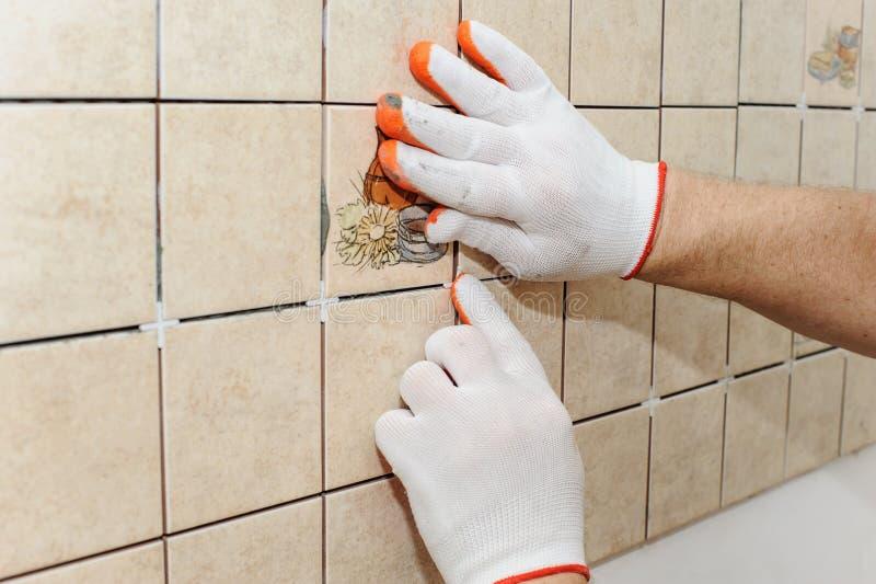 Lavoratore che mette le mattonelle sulla parete nella cucina immagine stock