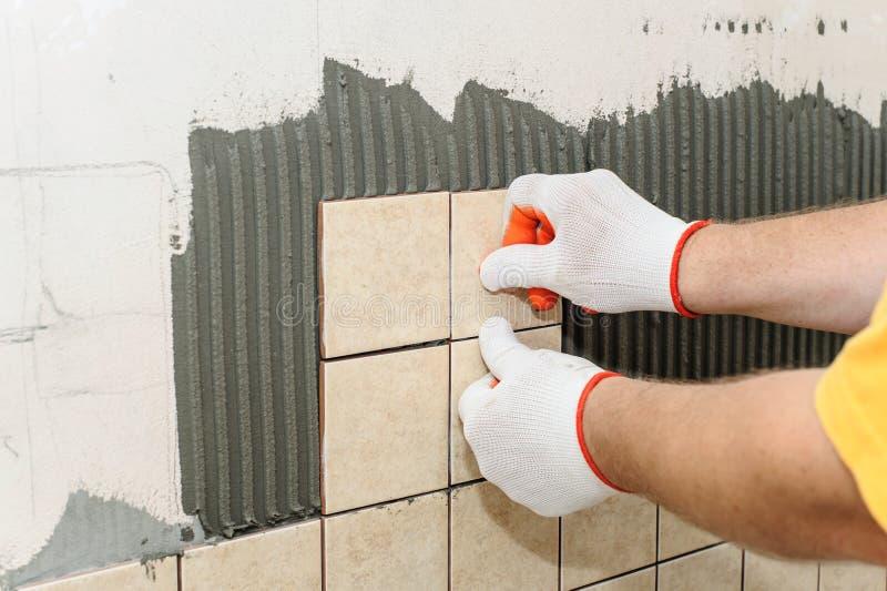 Lavoratore che mette le mattonelle sulla parete nella cucina fotografie stock libere da diritti