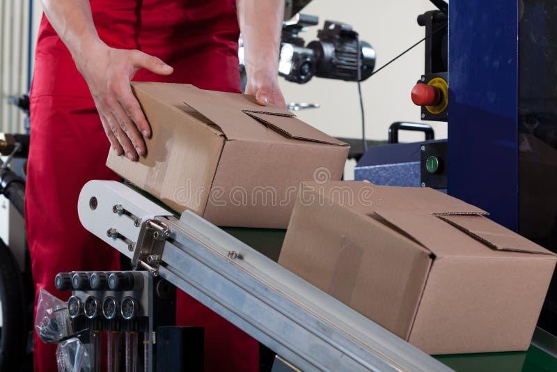 Lavoratore che mette una scatola sul nastro trasportatore fotografia stock libera da diritti