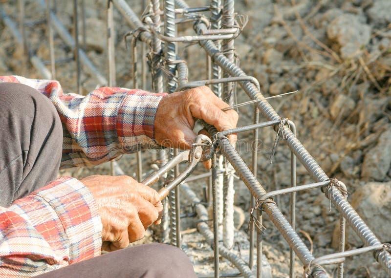 Lavoratore che per mezzo dello strumento d'acciaio per il piegamento dell'acciaio dalla sua mano per fare la costruzione del reci fotografia stock libera da diritti