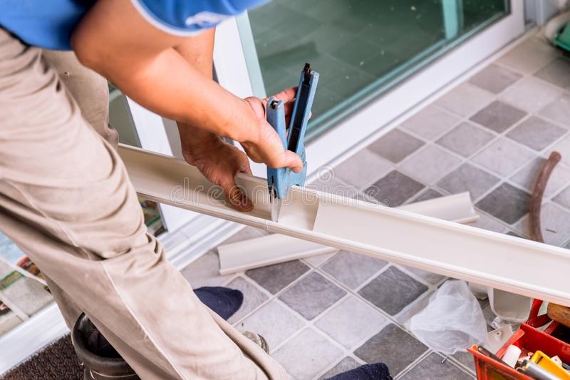 Lavoratore che per mezzo dello strumento per tagliare la ferrovia di plastica del cavo del tubo del PVC fotografia stock libera da diritti