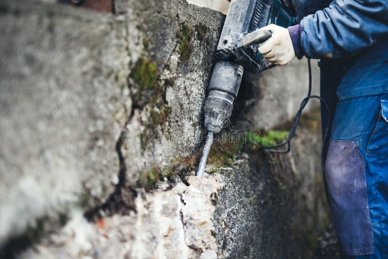 Lavoratore che per mezzo di un martello pneumatico per perforare nella parete lavoratore professionista nel cantiere fotografia stock libera da diritti