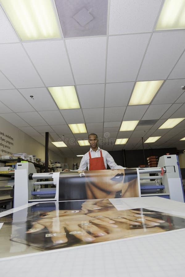 Lavoratore che prende gli stampati al torchio tipografico immagine stock