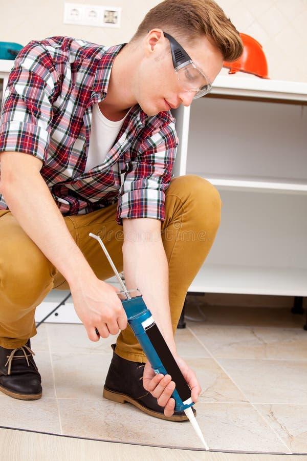 Lavoratore che ripara il pavimento fotografia stock libera da diritti