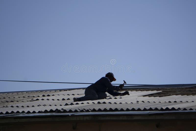 Lavoratore che ripara uno sharp del tetto fotografie stock
