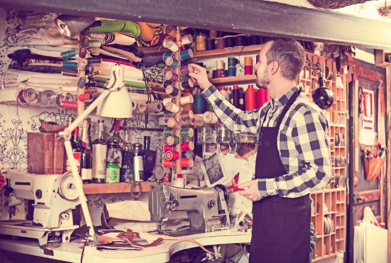 Lavoratore che sceglie filo per cucire fotografia stock