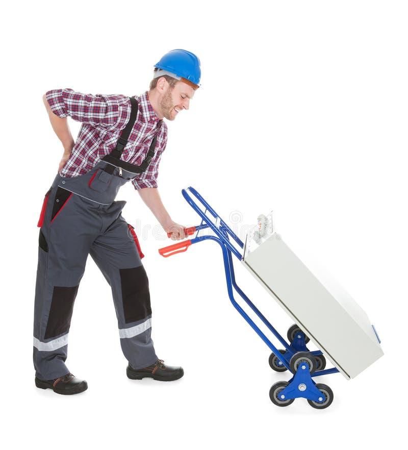 Lavoratore che soffre dal mal di schiena mentre spingendo macchinario fotografia stock libera da diritti