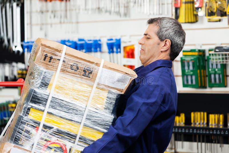 Lavoratore che solleva il pacchetto pesante dello strumento nel negozio dell'hardware fotografia stock