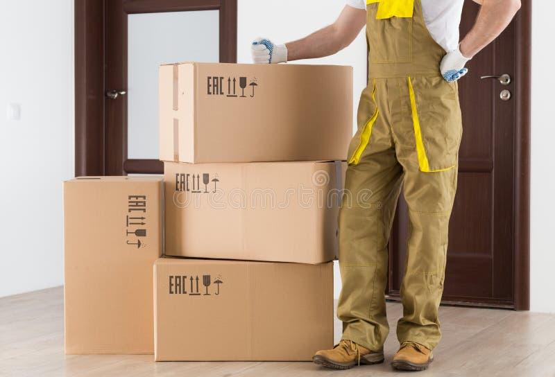 Lavoratore che sta vicino alle scatole consegnate in appartamento Parte posteriore di consegna immagine stock