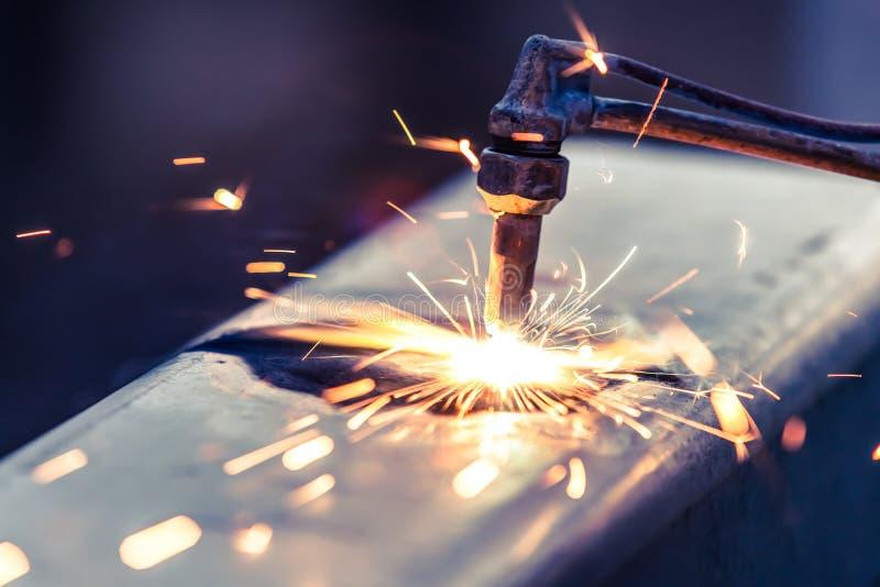 Lavoratore che taglia tubo d'acciaio facendo uso della torcia del metallo fotografia stock