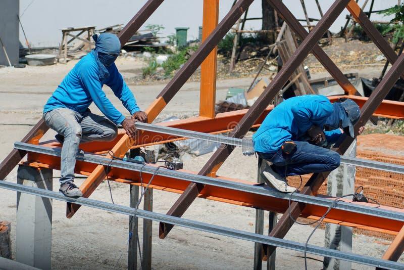 Lavoratore che tiene trapano elettrico che funziona e che installa struttura del tubo d'acciaio Galvanized, acciaio del tetto sul immagini stock