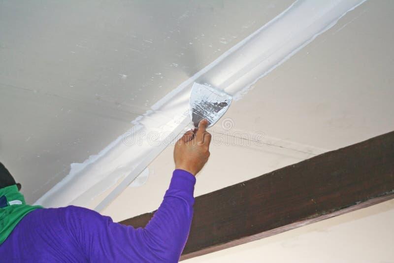 Lavoratore che usando il gesso del gesso sul coltello di mastice al soffitto fotografia stock