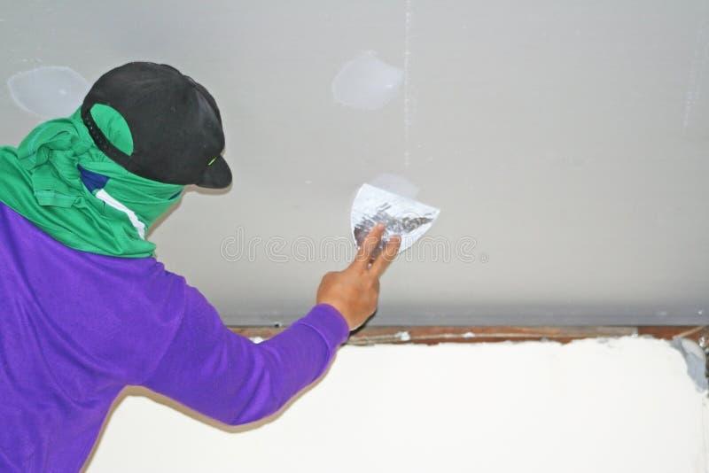 Lavoratore che usando il gesso del gesso sul coltello di mastice al soffitto fotografia stock libera da diritti