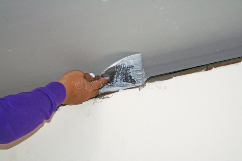 Lavoratore che usando il gesso del gesso sul coltello di mastice al soffitto immagine stock libera da diritti