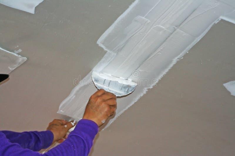 Lavoratore che usando il gesso del gesso sul coltello di mastice al soffitto immagini stock