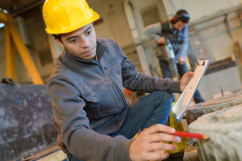 Lavoratore con il casco che lavora dentro la fabbrica moderna fotografia stock libera da diritti