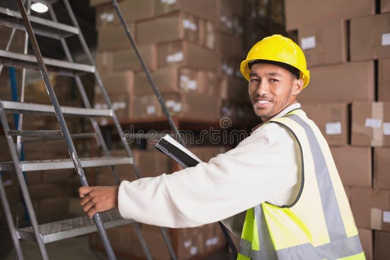 Lavoratore con il diario in magazzino immagine stock