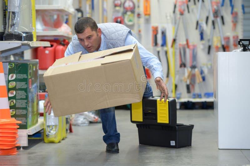 Lavoratore con il mal di schiena mentre sollevando scatola in magazzino fotografia stock libera da diritti