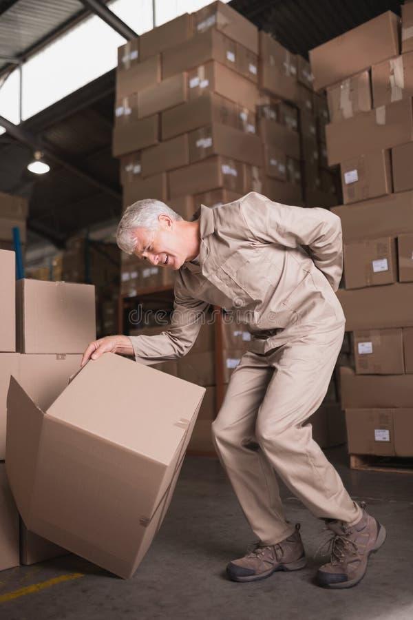 Lavoratore con il mal di schiena mentre sollevando scatola in magazzino fotografie stock