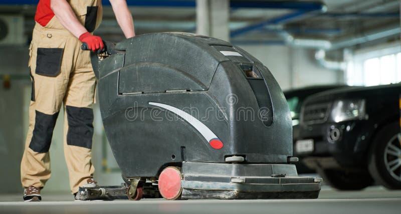 Lavoratore con il pavimento di pulizia della macchina in parcheggio fotografie stock