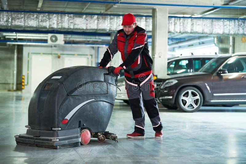 Lavoratore con il pavimento di pulizia della macchina in parcheggio fotografia stock libera da diritti
