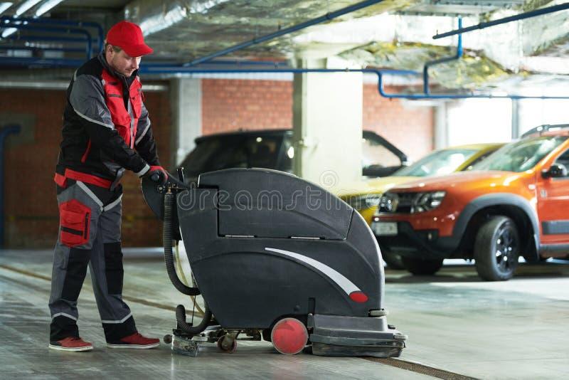 Lavoratore con il pavimento di pulizia della macchina in parcheggio immagine stock