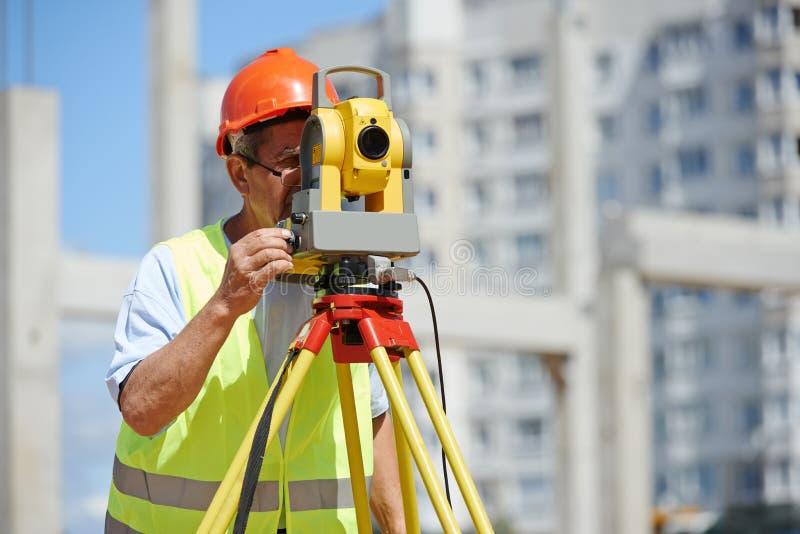 Lavoratore con il teodolite fotografie stock