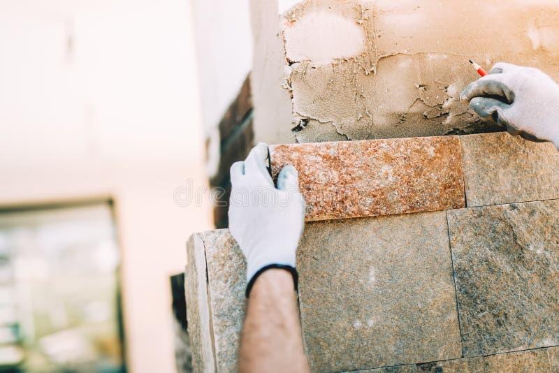 lavoratore con le mattonelle di pietra nel cantiere dettagli della muratura sulla parete esterna con il knifeworker del mastice d fotografie stock libere da diritti