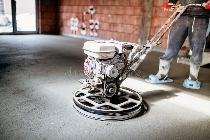 Lavoratore con lo strumento della cazzuola di potere che finisce pavimento di calcestruzzo, tirata, superficie di calcestruzzo re fotografia stock