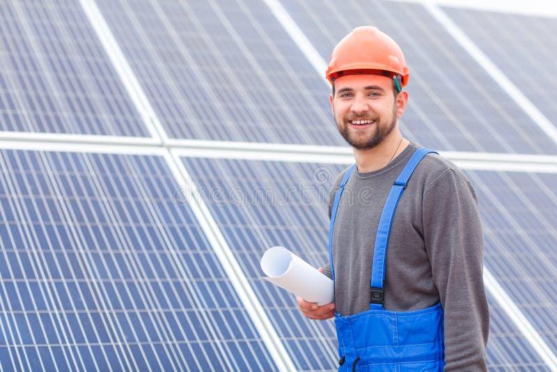 Lavoratore con una carta in sua mano e un casco sulla sua testa contro un fondo dei pannelli solari immagini stock libere da diritti
