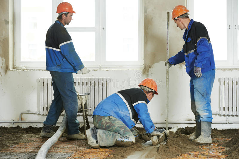 Lavoratore concreto degli intonacatori sul lavoro del pavimento fotografia stock libera da diritti