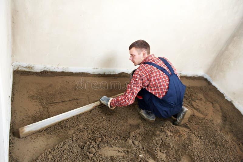 Lavoratore concreto dell'intonacatore sul lavoro del pavimento fotografie stock libere da diritti