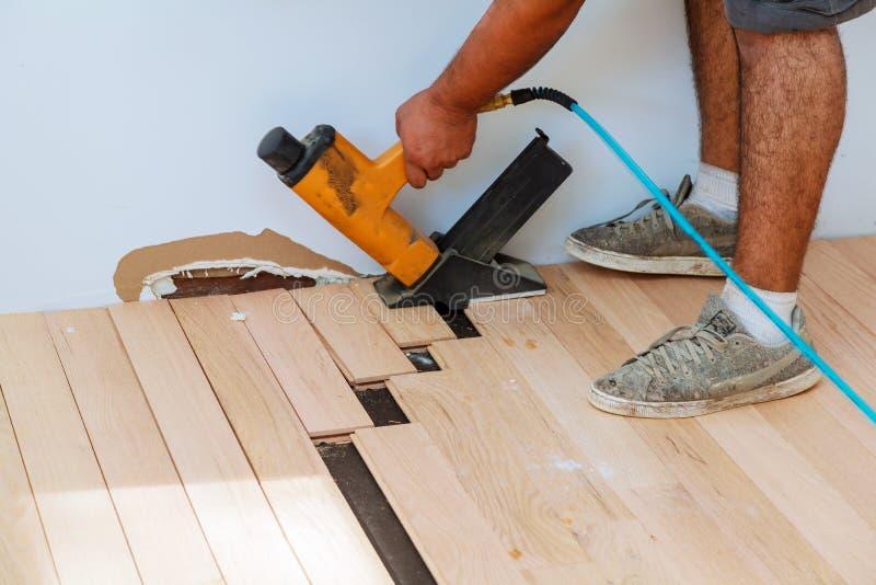 Lavoratore del carpentiere che installa il bordo di legno del parquet con il martello fotografia stock libera da diritti