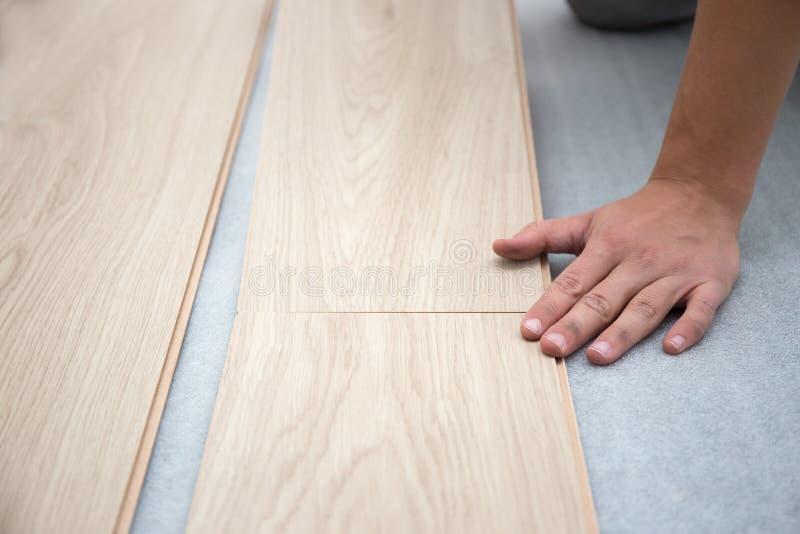 Lavoratore del carpentiere che installa pavimentazione laminata nella stanza fotografia stock