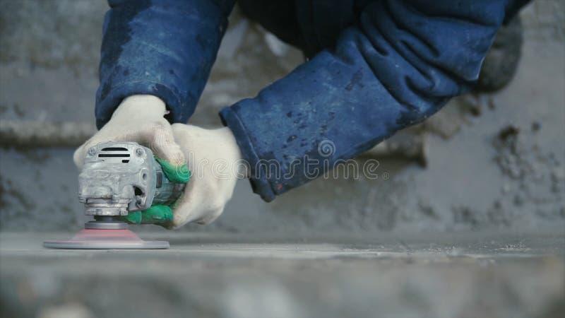 Lavoratore del costruttore con il muro di cemento di rifinitura di taglio a macchina della smerigliatrice al cantiere clip Il lav fotografia stock