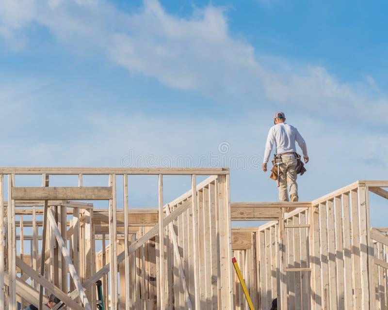 Lavoratore del costruttore del roofer di retrovisione sulla costruzione di legno delle capriate del tetto immagine stock libera da diritti