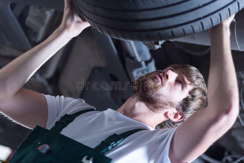 Lavoratore del distributore di benzina che controlla gomma immagine stock
