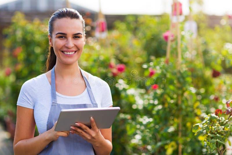 Lavoratore del Garden Center che per mezzo della compressa digitale fotografia stock
