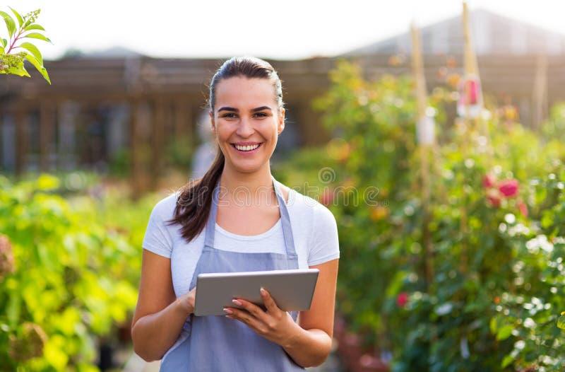 Lavoratore del Garden Center che per mezzo della compressa digitale immagini stock
