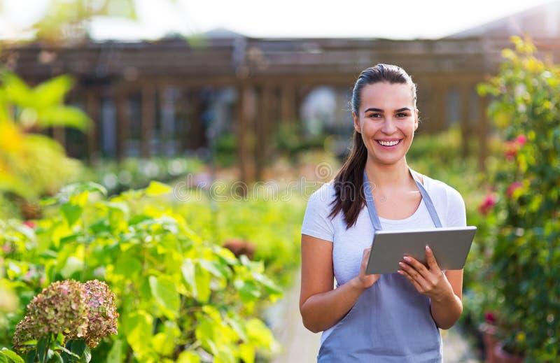 Lavoratore del Garden Center che per mezzo della compressa digitale immagini stock libere da diritti
