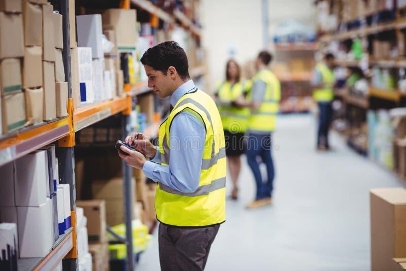 Lavoratore del magazzino che per mezzo dell'analizzatore della mano fotografia stock libera da diritti