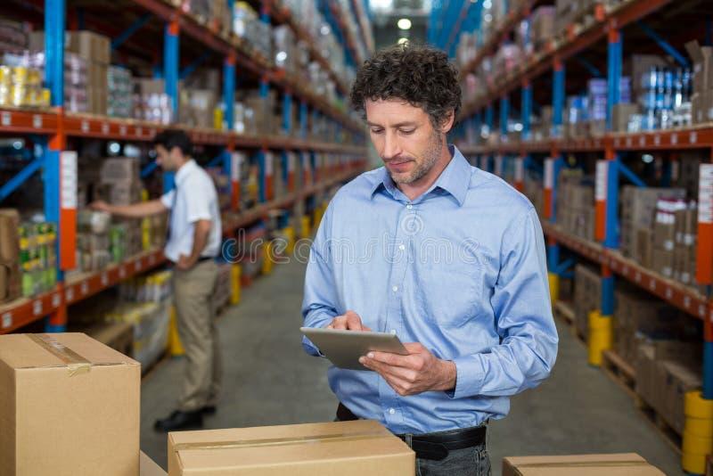 Lavoratore del magazzino che per mezzo della compressa digitale immagine stock